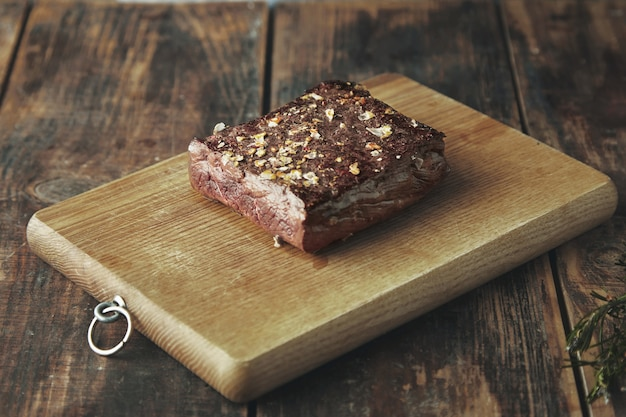 Закройте жареное квадратное мясо со специями и солью, изолированное на деревянной доске на винтажном столе