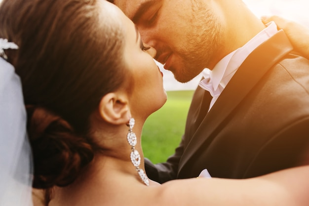Close-up of groom and bride before kissing