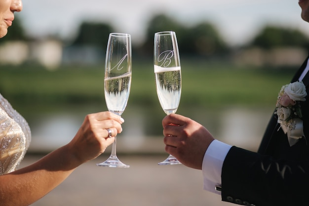 Close-up of groom and bride hold glasses of champagne.