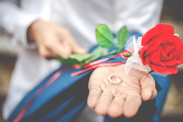 Close-up the groom holding wedding ring on the palm with red rose