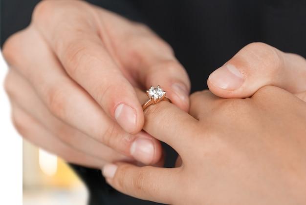 花嫁に結婚指輪を置く新郎を閉じる