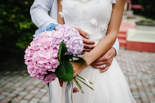 Close-up of groom's hand holding bride's and stylish wedding bouquet of flowers.