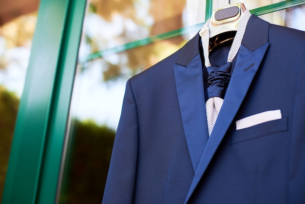 Close-up of groom's new blue suit and tie hanging on a hanger