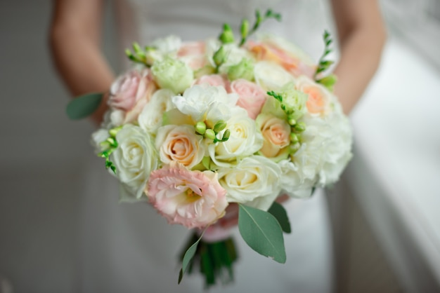 Close-up groom in a suit and the bride in a white dress are standing and holding a bouquet of peach roses