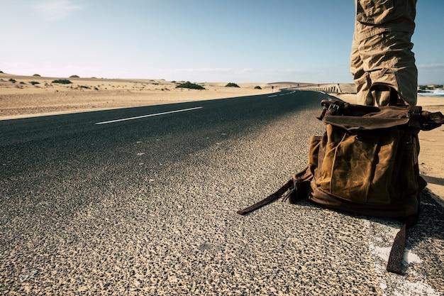 革のバックパック旅行で男の地上の視点をクローズアップし、車が一緒に旅行を共有するのを待つ