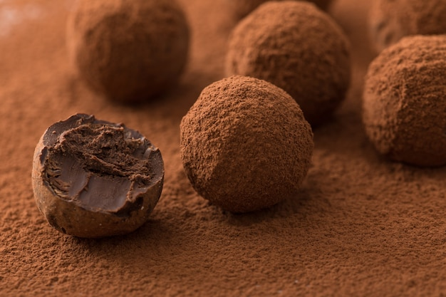 Close up of group of appetizing black chocolate truffles covered in cocoa dust.
