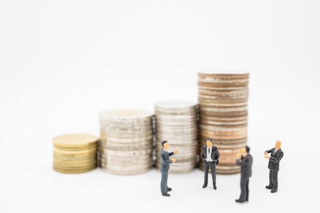 Close up of group of businessman minature figures standing and clap applaud appreciation with stack of coins.