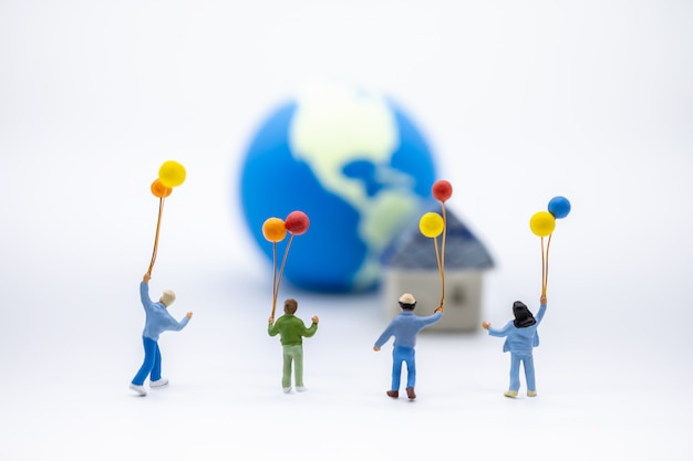Close up of group children miniature figure playing and holding colorful balloon on white