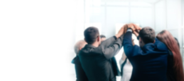 Close up. a group of corporate employees showing their unity. the concept of teamwork. background in blur with copy space