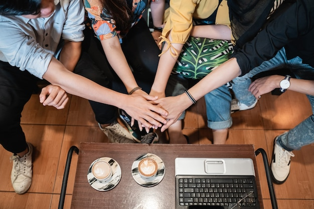 Close up group of friends joining hands with unity teamwork concept