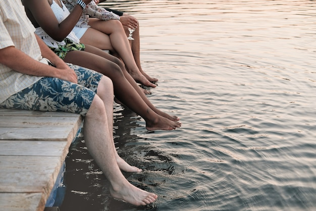 Close-up of group of friends sitting on a pier and wetting their feet in the water in summer day
