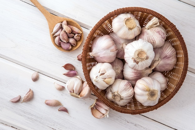 Close up group of garlic on a white wooden table board
