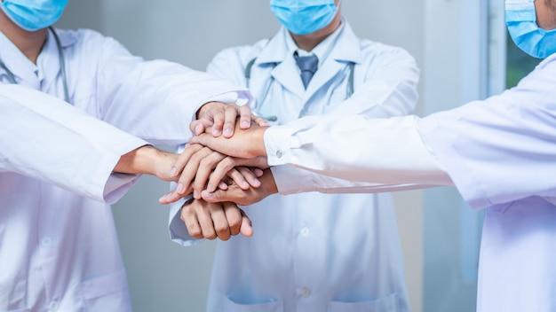 医師と看護師のグループの手を閉じる手を閉じます。成功の仕事とチーム、調和、医師の成功のバナーの背景の信頼のための病院でのチームワーク。