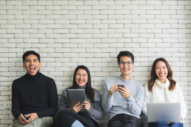 Close up group of millennial generation holding modern gadget devices and sitting on white wall room