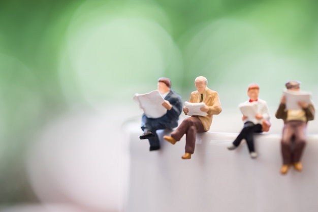 Close up of group miniature mini figures man and woman sit and read a book and a newspaper on cup