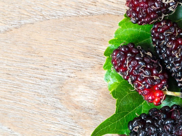 Close up group of mulberries with a green leaves on the wooden table.