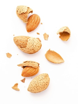 Закройте группу орехов миндаля с раковиной и треснутой раковиной миндаля изолированной на белой предпосылке.