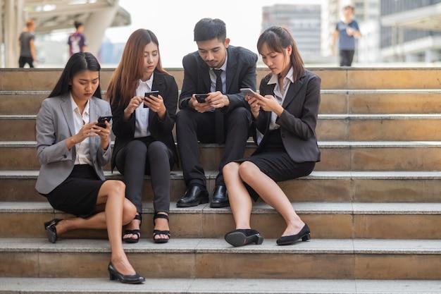 都市のスマートフォンを使用してリラックスしたビジネス人々のグループを閉じます