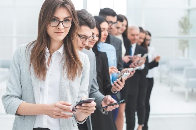 閉じる。スマートフォンが並んでいるビジネスマンのグループ