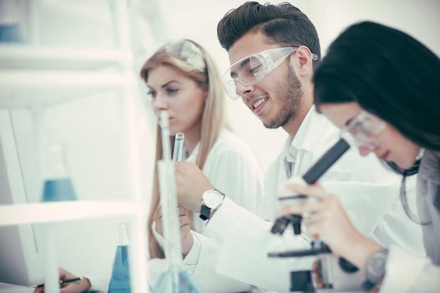 閉じる。コロナウイルスに関するデータを分析する医師のグループ。科学と健康