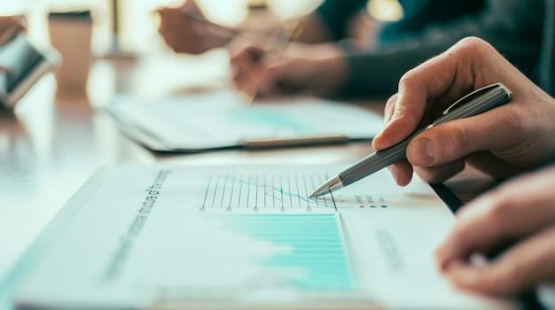閉じる。財務チャートを分析する従業員のグループ。ビジネスコンセプト。