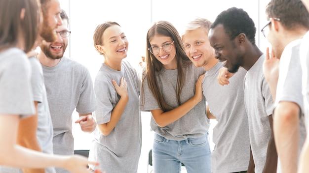 閉じる。明るい部屋に立っている幸せな若者のグループ