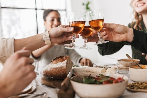 손에 와인 잔을 들고 국제 친구의 그룹을 닫습니다