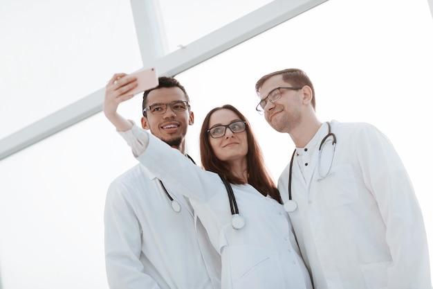 셀카를 찍는 의사들의 그룹을 닫습니다. 사람과 기술