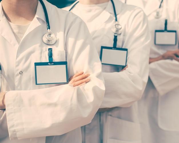 閉じる。空白のバッジが一列に並んでいる医者のグループ。コピースペース付きの写真。