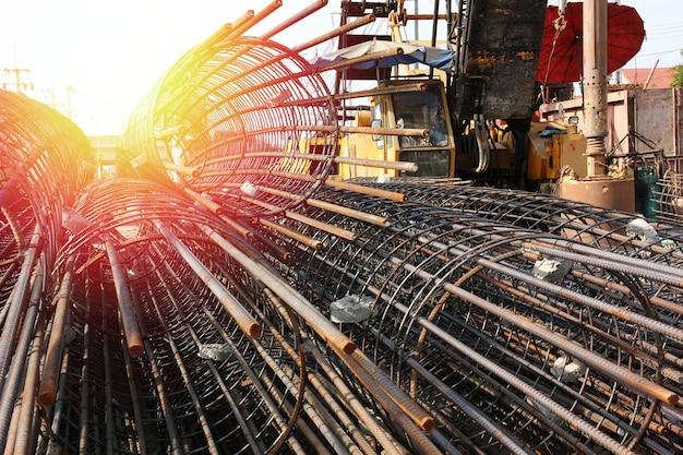 鉄骨構造のクローズアップグループは、大きな建設現場で退屈な杭を作ります