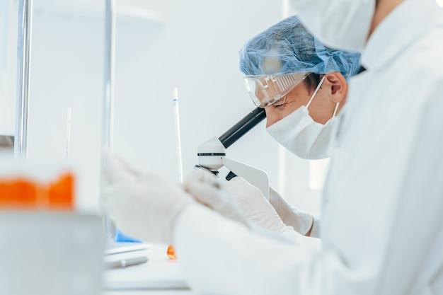 Закройте вверх. в лаборатории работает группа вирусологов в защитной одежде. фото с копировальным пространством.