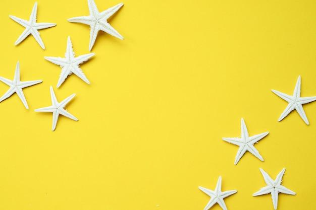 黄色の背景に白い星の魚のグループを閉じます