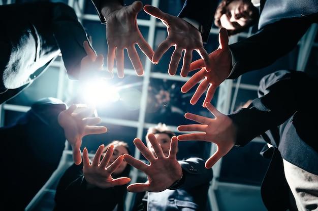 Закройте группу молодых деловых людей, соединяющих ладони в круге