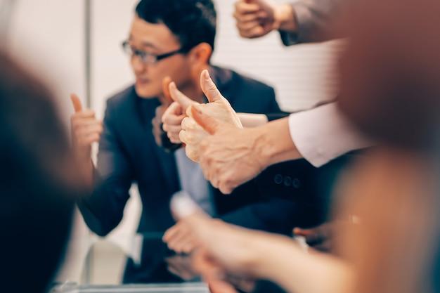 閉じる。親指を立てる若いビジネスマンのグループ。事業背景