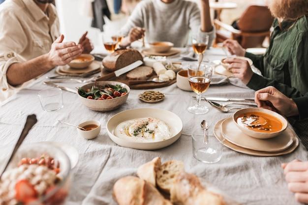 아늑한 카페에서 맛있는 음식과 와인 잔으로 가득 찬 테이블에 앉아있는 젊은 사람들의 그룹을 닫습니다.