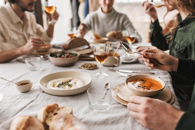 아늑한 카페에서 점심을 먹고 맛있는 음식으로 가득 찬 테이블에 앉아 젊은 사람들의 그룹을 닫습니다