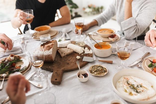 함께 점심을 먹고 맛있는 음식으로 가득 찬 테이블에 앉아 젊은 사람들의 그룹을 닫습니다