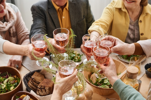 Close-up of group of people holding glasses with red wine and toasting during dinner at the table