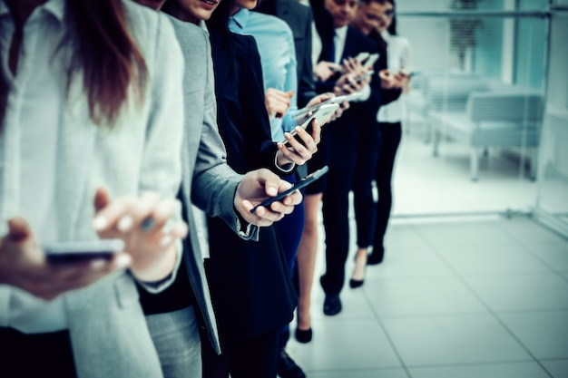 Close up. a group of young business people looking at their smartphone screens