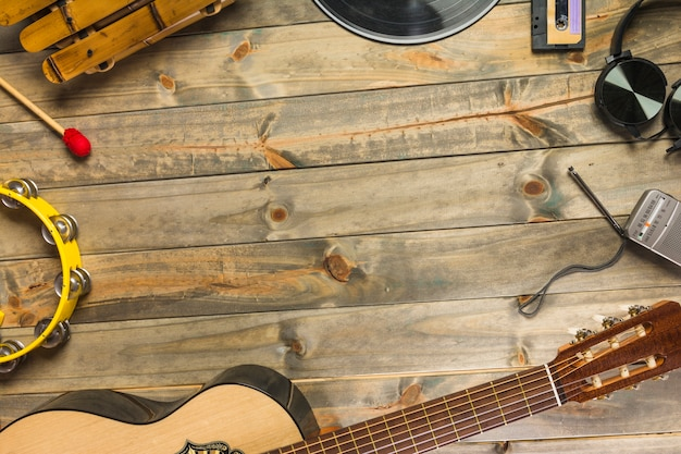 Close-up of guitar; headphone; tambourine; xylophone; headphone and radio on wooden table with space for text