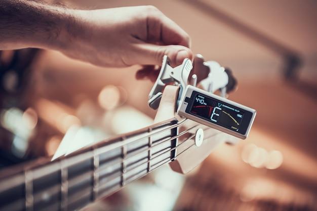 Close up. guitarist tunes guitar with tuner clip.