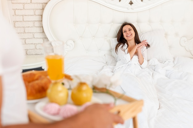 Close-up guy bringing breakfast to his girlfriend