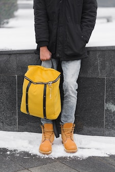 Close-up guy holding his yellow backpack