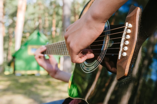 Close-up of a guy playing the guitar. against the background of a forest and a house in nature.