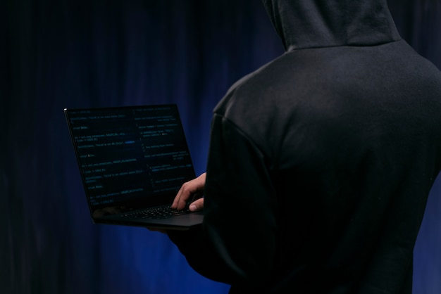Close up hacker holding laptop