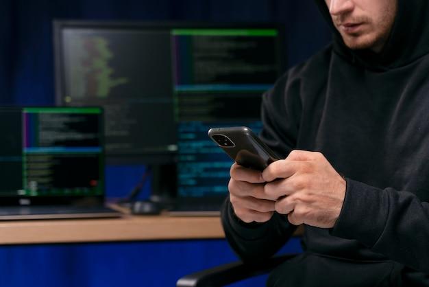 Close up hacker holding phone