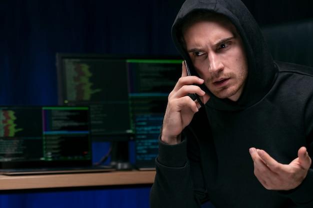 Крупным планом хакер разговаривает по телефону