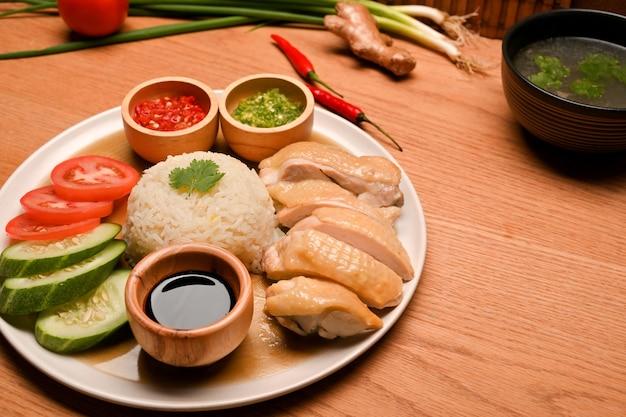 新鮮な野菜と木製のテーブルの上のクローズアップ海南チキンライス。アジアのグルメ料理のコンセプト