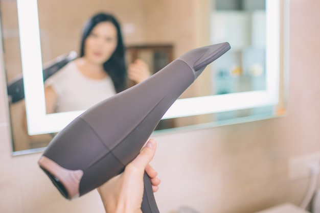Close up of hair dryer. woman holds it in hand. she looks in mirror. brunette does a hairdressing.