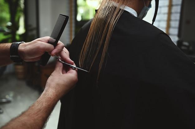 Стрижка крупным планом профессиональным стилистом. парикмахер стрижет волосы в салоне красоты